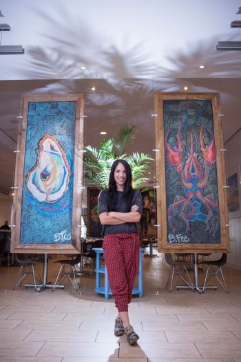 Becky and her art as featured in Borgne Restaurant.